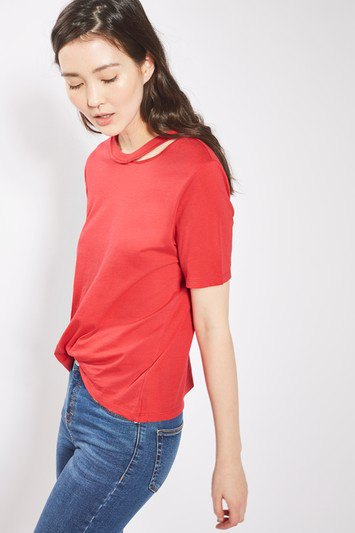 red cut out t shirt with blue slim cut jeans and sneakers