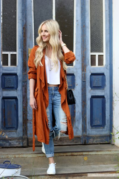 red longline trench coat with ripped boyfriend jeans and white sneakers