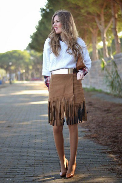 white cable knit sweater with metallic belt and knee length fringe skirt