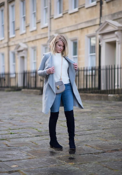 white sweater with grey long coat and blue tall jeans