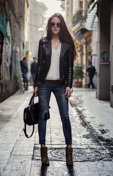 black moto jacket with white chiffon v neck blouse and leopard print boots