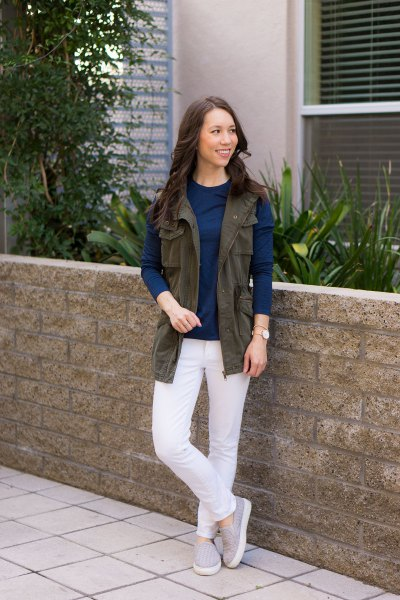 brown utility vest with navy blue long sleeve top and white jeans