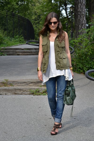green utility vest with white sleeveless tunic top and cuffed blue jeans