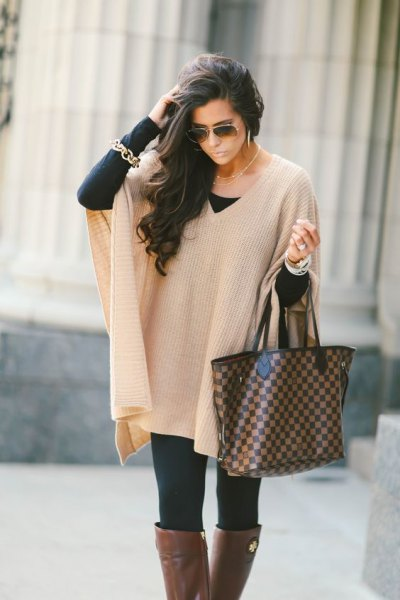ivory ribbed cape sweater with black leggings and grey over the knee fall boots