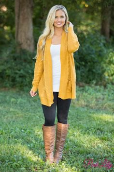 mustard yellow longline sweater jacket with brown knee high leather boots