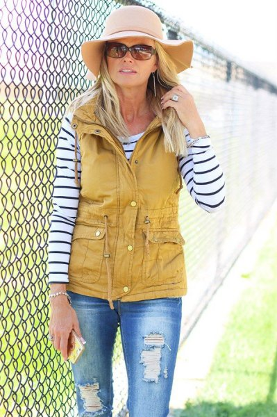 mustard yellow utility vest with black and white striped long sleeve tee