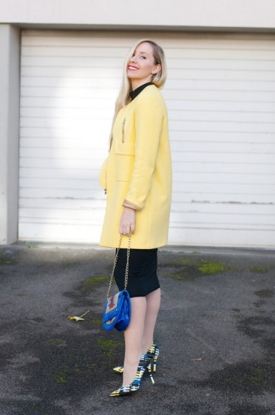 pale yellow long wool coat with black knee length shift dress