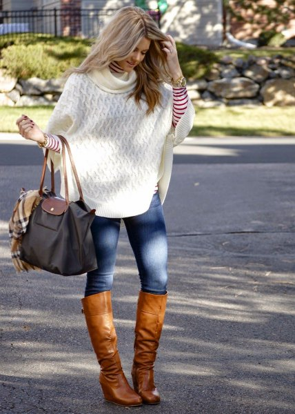 white cable knit poncho sweater with blue skinny jeans and brown leather knee high boots