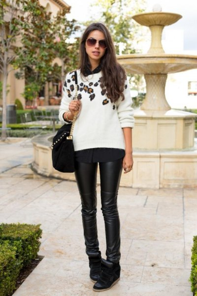 white floral printed sweater with black leather leggings and wedge sneakers