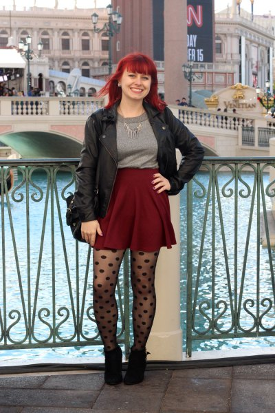 black leather jacket with grey sweater and burgundy high rise mini skirt