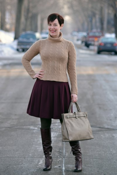 form fitting green turtleneck sweater with black pleated skirt and brown tights