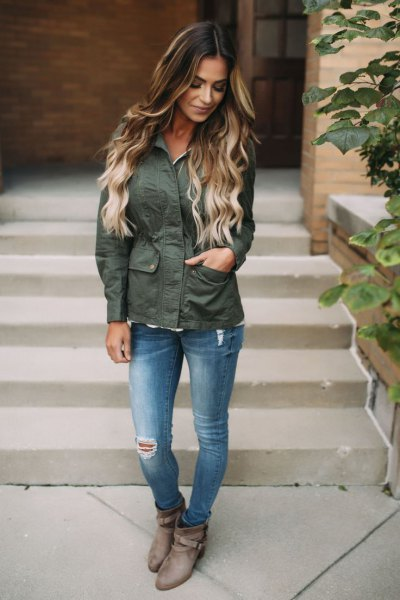 grey hiking jacket with blue ripped slim fit jeans and boots