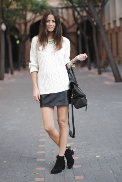 white cable knit sweater with black leather skirt and heeled mini boots