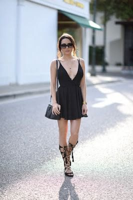 black deep v neck fit and flare cocktail dress with knee high strappy sandals