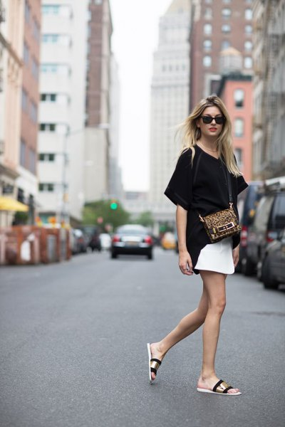 black oversized t shirt with white mini skirt and black and gold summer sandals