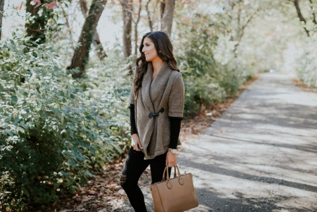 grey half sleeve sweater with black long sleeve top and brown leather bag