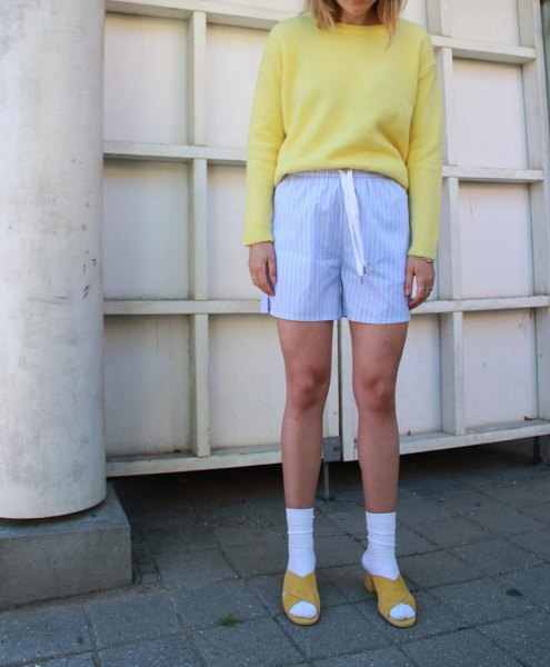 orange sweatshirt with sky blue striped knit shorts and sandals