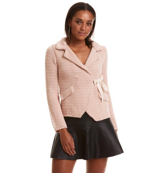 pale pink knit jacket with black mini skater leather skirt