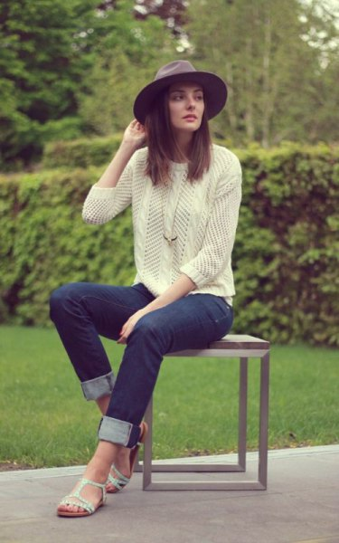 pale yellow knit sweater with dark blue cuffed slim fit jeans and white sandals