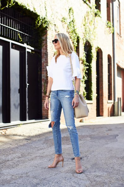 white ruffle sleeve blouse with light blue ripped skinny jeans