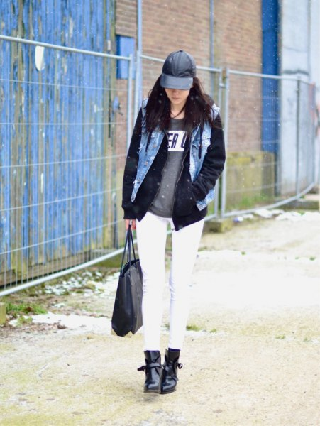 black leather baseball cap with denim vest and graphic sweater