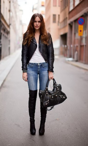 black slim fit leather jacket with blue skinny jeans and flat long boots