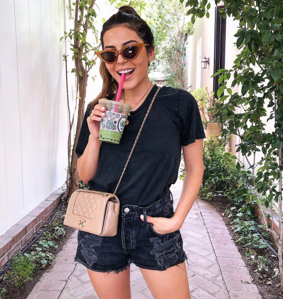 black t shirt with ripped denim shorts and pink purse