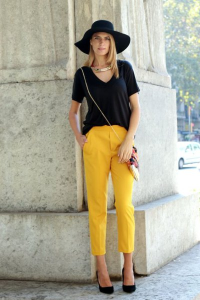 black v neck t shirt with floppy hat and cropped yellow pants