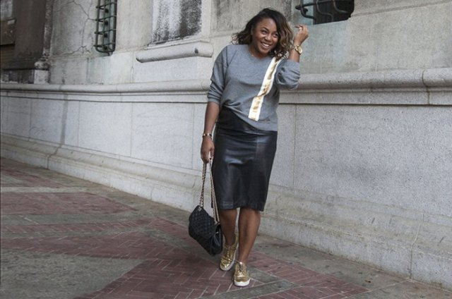 grey sweater with black midi leather skirt and gold low top sneakers