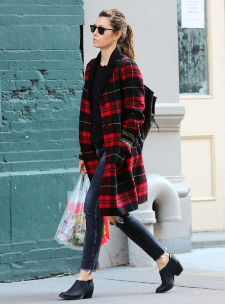 red and black midi length plaid coat with dark blue skinny ankle jeans