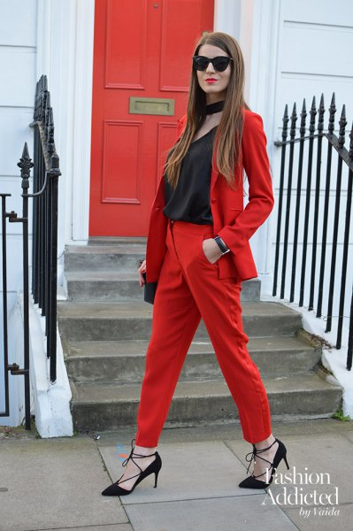 red suit with black scoop neck top and choker