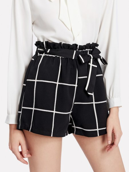 white button up blouse with black tie plaid shorts