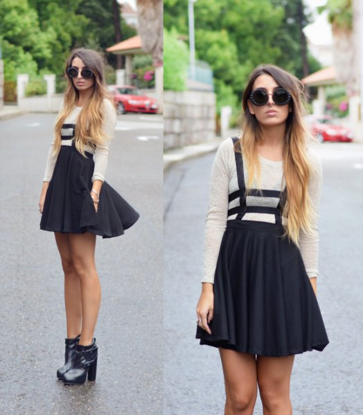 white long sleeve t shirt with mini pleated black skirt and ankle heeled boots