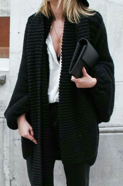 black chunky cable knit cardigan with white blouse and clutch bag