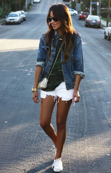 blue denim jacket with camo t shirt with ripped white jean shorts