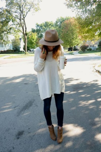 blush hat with white oversized sweater and camel suede ankle boots