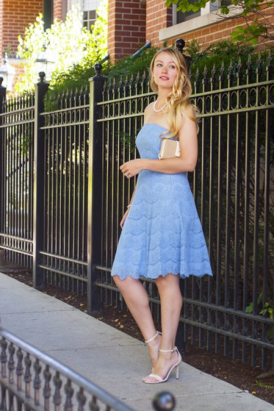 light blue fit and flare strapless midi dress with blush clutch bag