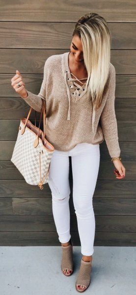 tan lace up neckline sweater with white skinny jeans