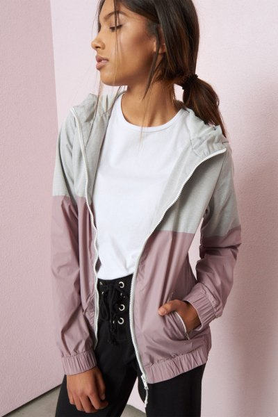 white and light grey color block nike windbreaker with black lace up jeans
