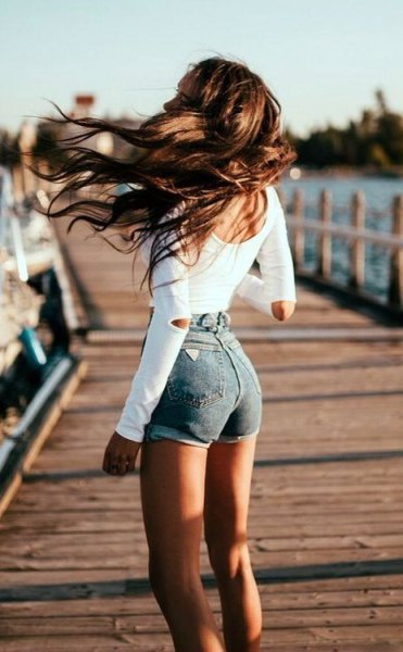 white form fitting open elbow long sleeve tee with blue skinny jean shorts