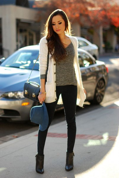 white knit cardigan with grey scoop neck knit sweater and black skinny jeans