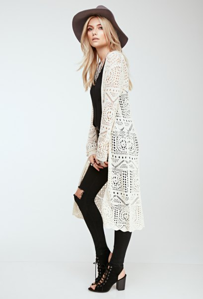 white long crochet cradigan with black skinny ripped jeans