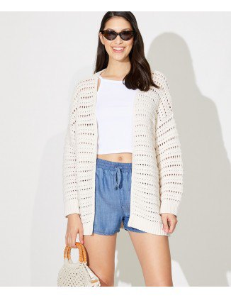 white oversized crochet cardigan with cropped tee and blue elastic waist shorts