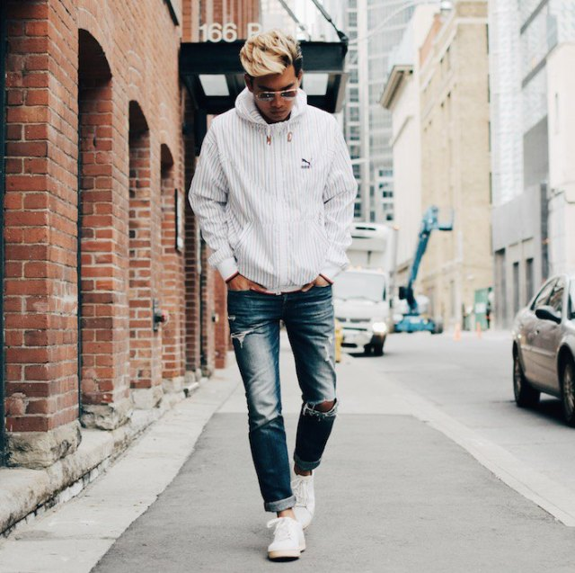 white windbreaker with blue cuffed washed straight leg jeans