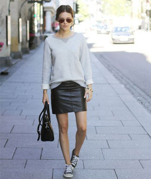 grey sweatshirt with mini moto skirt and black leather sneakers