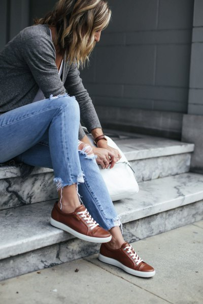 grey t shirt with light blue slim fit jeans and brown leather sneakers