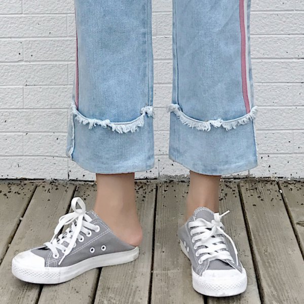 light blue cuffed pleated cropped jeans with grey and white canvas sneakers