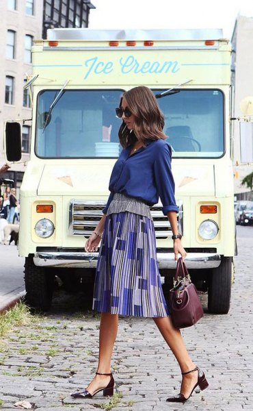 navy blue shirt with printed midi skirt and black heels