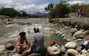 Una familia colombiana que cruzó desde Venezuela hacia Colombia lava su ropa en el río Tachira. / SCHNEYDER MENDOZA (EFE)
