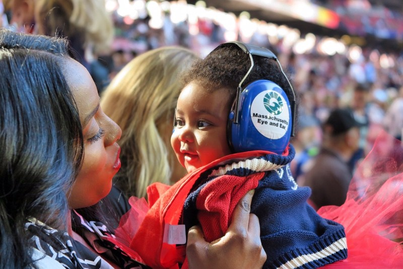 Young girl wearing hearing protection at football game